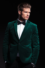side view of a young elegant man in green velvet suit