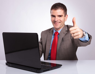 young business man shows thumb up from behind laptop