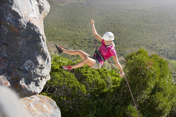 Female rock climber abseiling down rock face