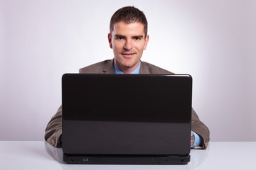 young business man smiles from behind laptop