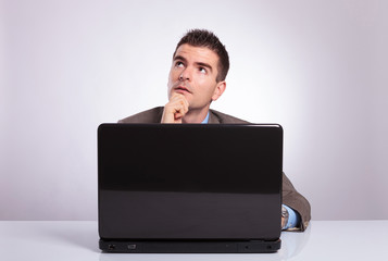 pensive young business man behind laptop looks away