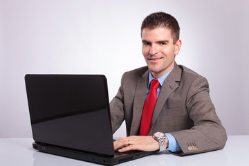 young business man looks at you while working on laptop