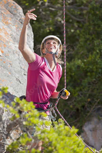 Smiling female rock climber looking up and gesturing