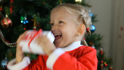 Laughing Child, Little Girl Shaking Gift by Christmas Tree