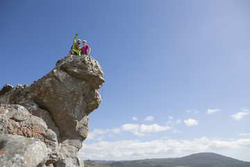 Rock climbers pointing and looking at view from on top of rock