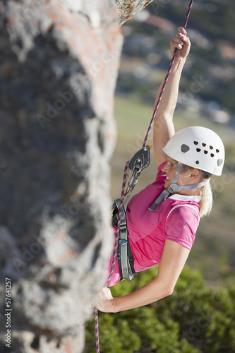 Female rock climber hanging from rope