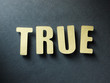 The word True on paper background