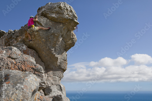 Male rock climber descending rock face
