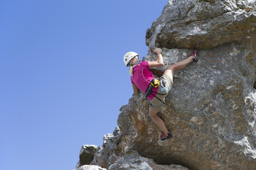 Female rock climber ascending rock face