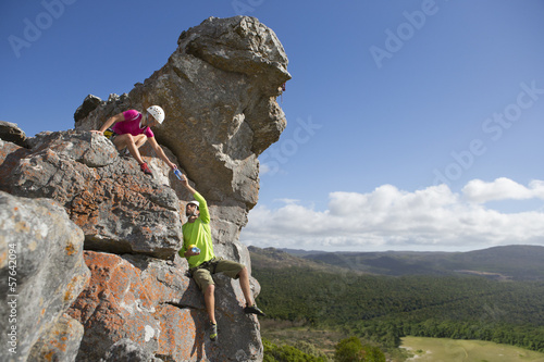 Male rock climber handing water bottle to woman on top of rock