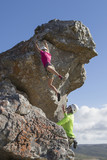 Female rock climber hanging from rock