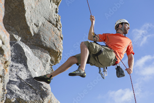 Male rock climber abseiling down rock face and looking back