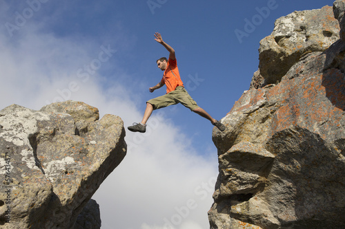Male rock climber jumping between rocks