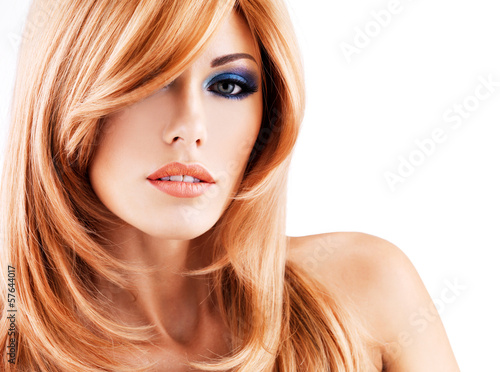 Portrait of a beautiful woman with long red hairs and blue makeu