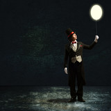 magician holding a glowing balloon