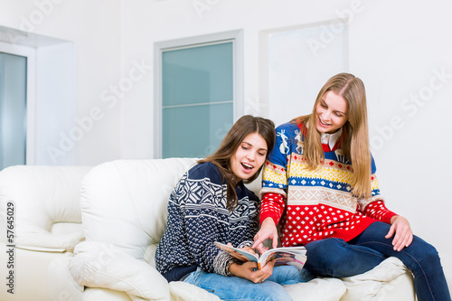 Two girls are reading magazine