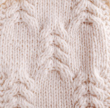 Close-up of knitted cloth with raised plaits.