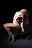 Naked girl bound to chair in the dark