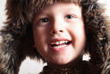 Funny smiling child in a fur hat. fashion kid. winter style