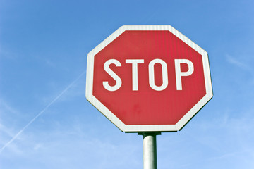 Stop road traffic sign over blue sky