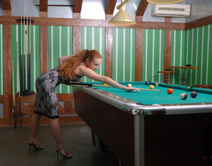 Attractive girl playing billiards
