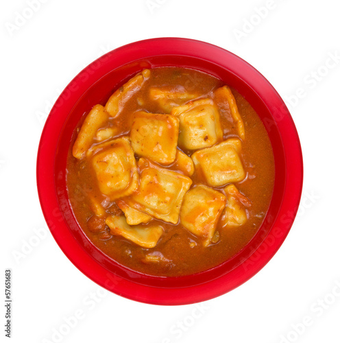 A large serving of ravioli in tomato sauce in a red bowl