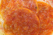 A very close view of cooked pepperoni on pizza