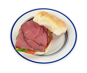 A roast beef bulky roll sandwich on a plate