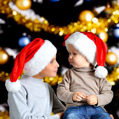 Portrait of two brothers in the new year Santa hats