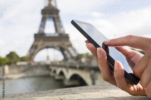 Woman in Paris using her cell phone in front of Eiffel Tower
