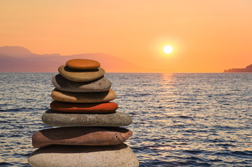 Stack of stones on beach at sunset