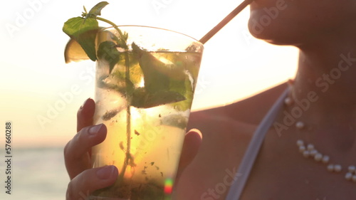 Woman enjoying a tropical mojito cocktail
