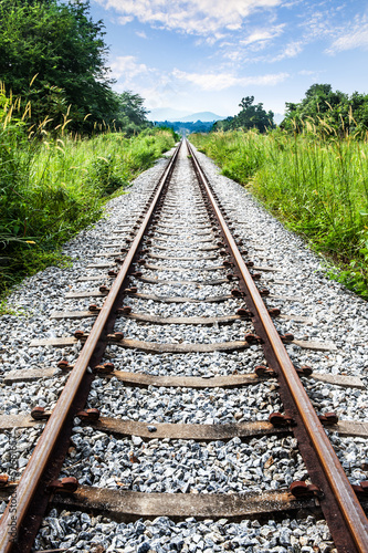 Poster Railway tracks with green grass,mountain & blue sky,Thailand
