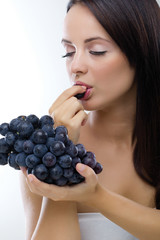 Beautiful woman eating fresh grapes