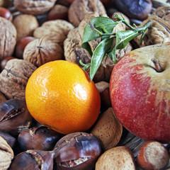 bunter teller mit mandarine, apfel und nüssen