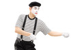 Male mime artist performing pulling virtual rope