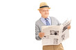 Senior man reading a newspaper and leaning against a wall