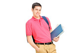 Smiling student holding books and leaning against wall