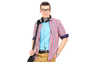 Male student with a shoulder bag and headphones posing