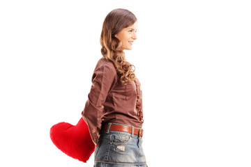 Young female holding a red heart behind and looking