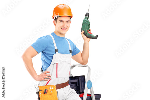 Manual worker on a ladder holding a drill