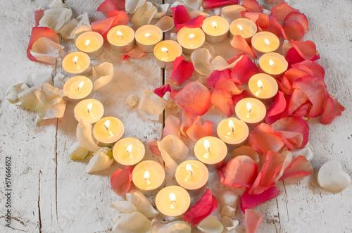 Liebe Grüße: Herz aus Rosenblütenblättern und Kerzen