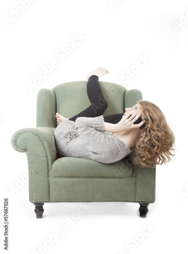 young pretty woman on the phone in armchair
