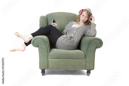 young pretty woman listening to music in armchair