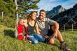 Paar macht Pause auf einer Wiese in den Bergen