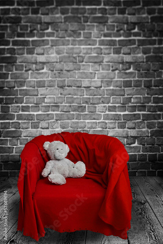 lonely teddybear sitting on a red chair
