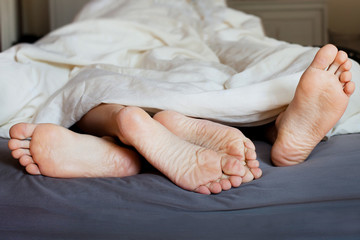 Lover's feet in the bed