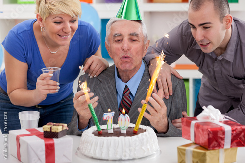 senior man blowing candles