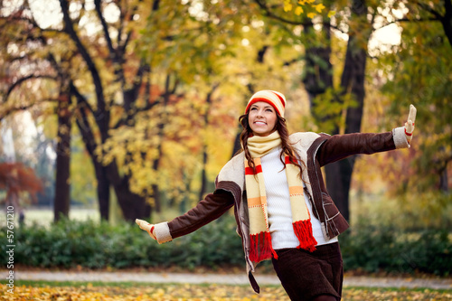 Young woman playing in autumn park