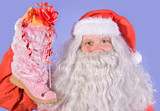 Santa Claus holding a shoe with gift on blue background